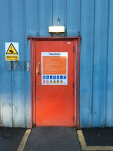 Sign installed at the entrance to a fitting shop, including site rules and H&S pictograms