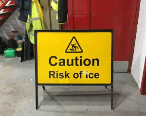 A temporary sign frame saying 'Caution, Risk of ice' with pictogram of man slipping